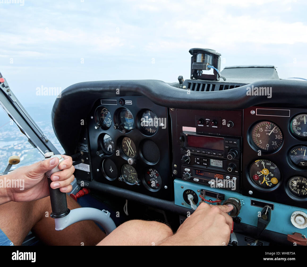 Cockpit view of a sports plane. Amateur pilot holding a hand control and throttle lever. Stock Photo