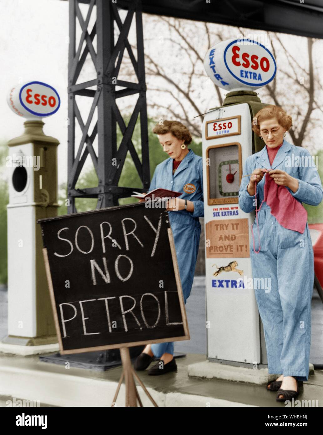 The unofficial strike of petrol tanker men is now seriously affecting London garages, many of which are today displaying Sold Out notices. At one Hendon garage, the girl assistants having no petrol to sell were whiling away their time on various activities such as reading and knitting.. . Picture shows Pauline Piercy and Rene Thursfield with a Sorry No Petrol notice in front of them. Stock Photo