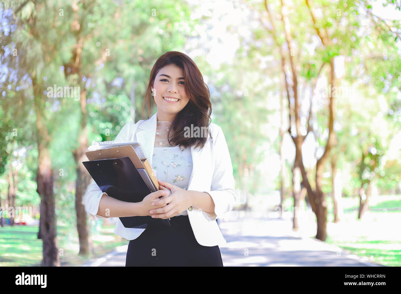 Portrait Of Smiling Young Woman Standing On Road Amidst Trees Stock Photo