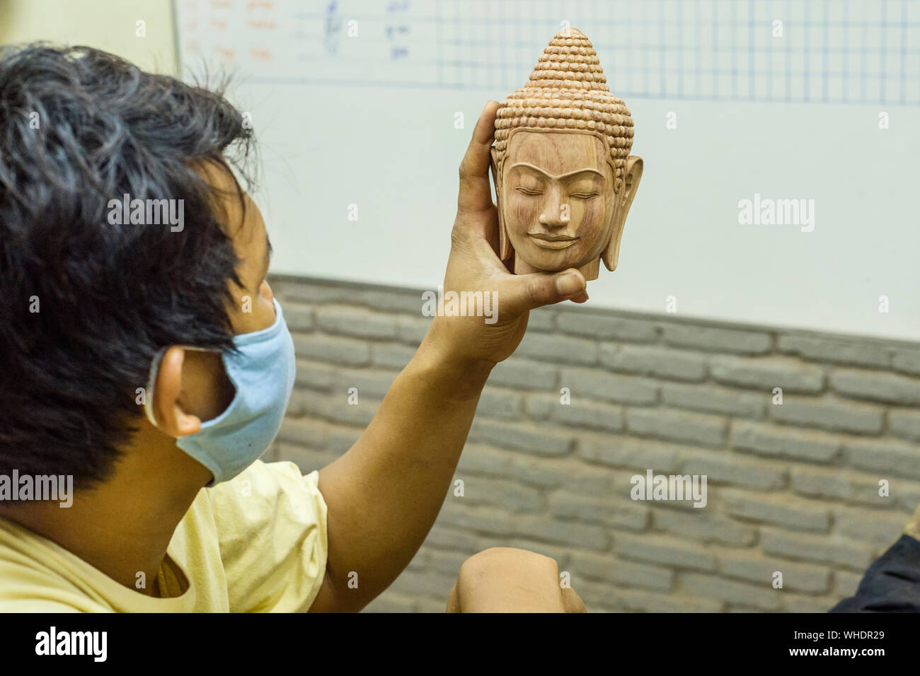 a sculptor of the Cambodian company of Angkor craftsmen cuts