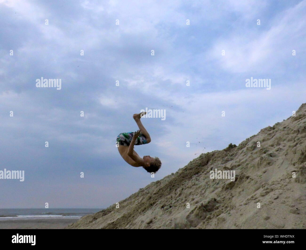 View Of Boy Somersaulting On Beach Stock Photo