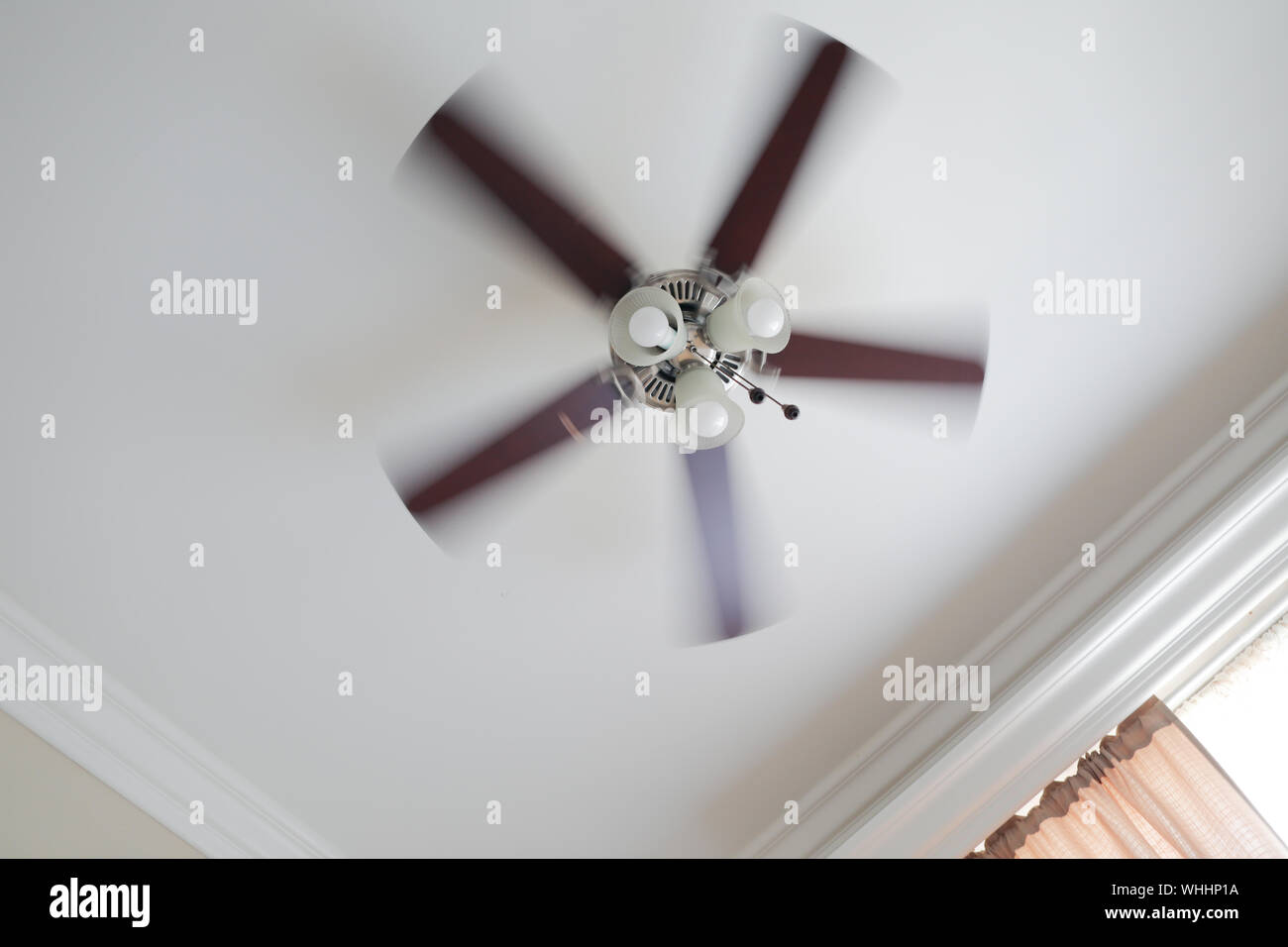 Ceiling fan with a ceiling lamp turned on, working with blurred blades in a living room, ceiling with moldings, curtain with shades and rods. Stock Photo