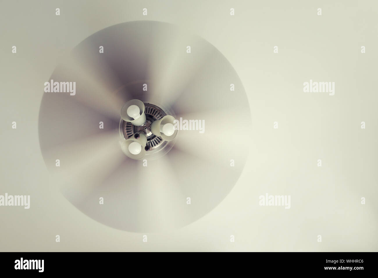 A working ceiling fan on a white ceiling, close up with blurred fan blades, three lamps, daytime. Stock Photo