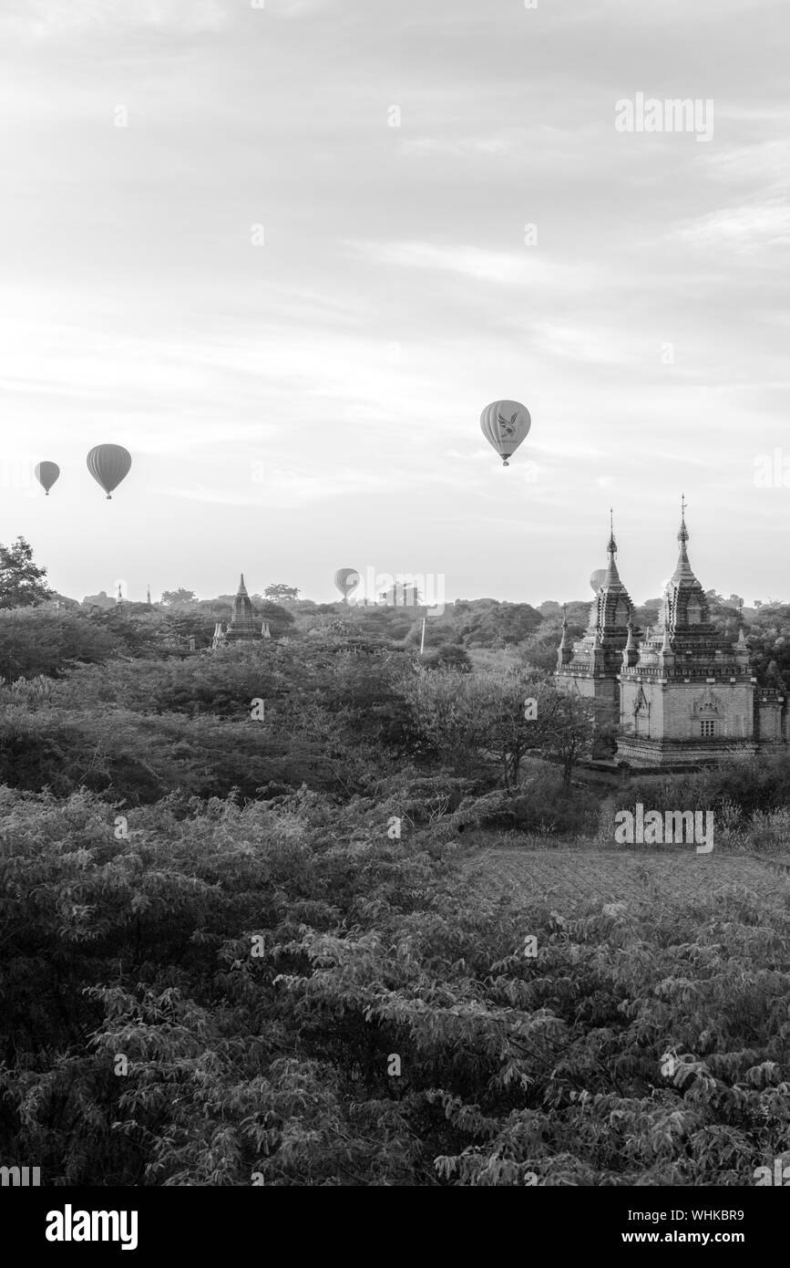 BAGAN, MYANMAR - 06 DECEMBER, 2018: Black and white picture of scenic view of colorful sky with old buddhist temples and hot air balloons in Bagan, lo Stock Photo