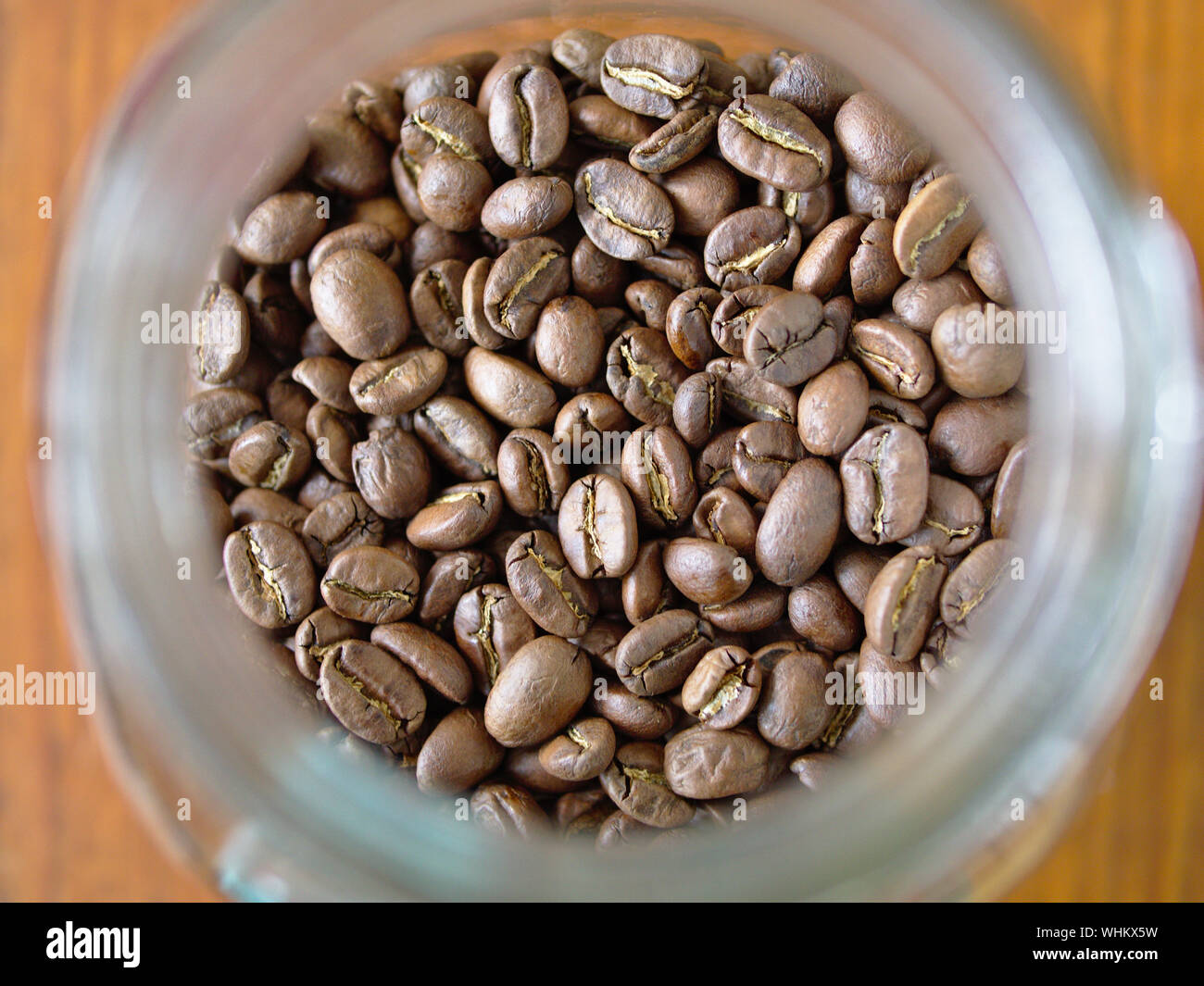 Roasted (medium) coffee beans in a glass jar. About to be scooped, ground & AeroPressed into a delicious cup of Americano type coffee. Stock Photo