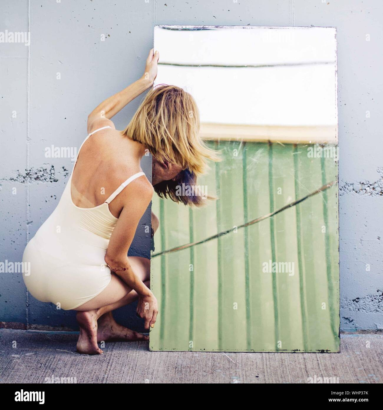 Rear View Of Woman Looking At Mirror Against Wall Stock Photo