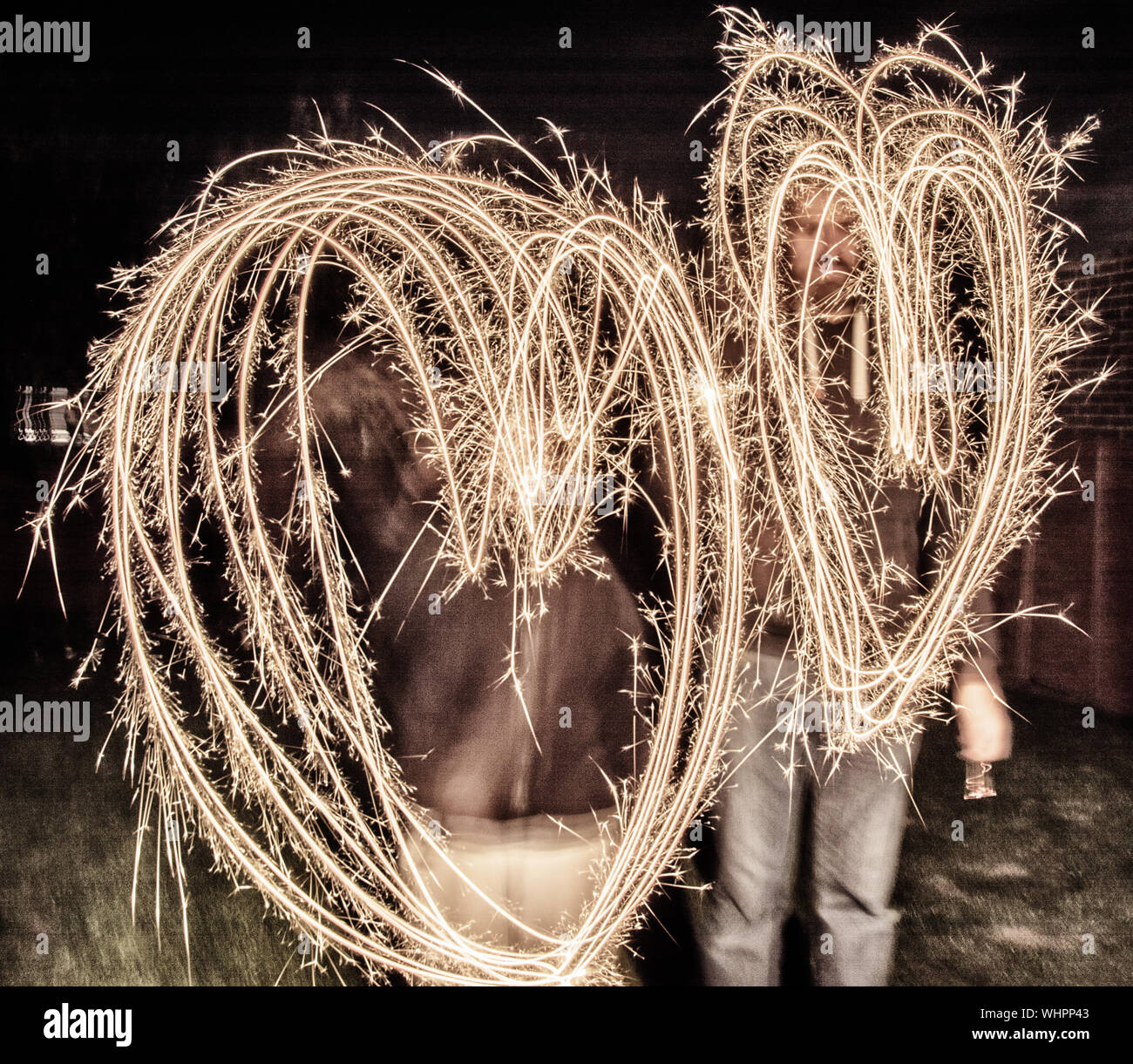 Men Making Heart Shape With Sparklers At Night Stock Photo