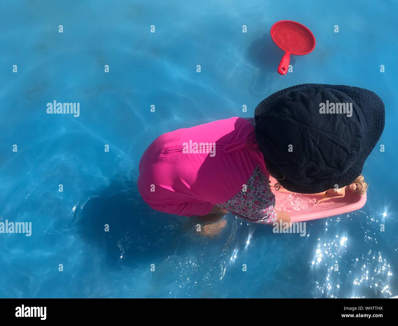 High Angle View Of Girl Playing With Toys In Swimming Pool Stock Photo
