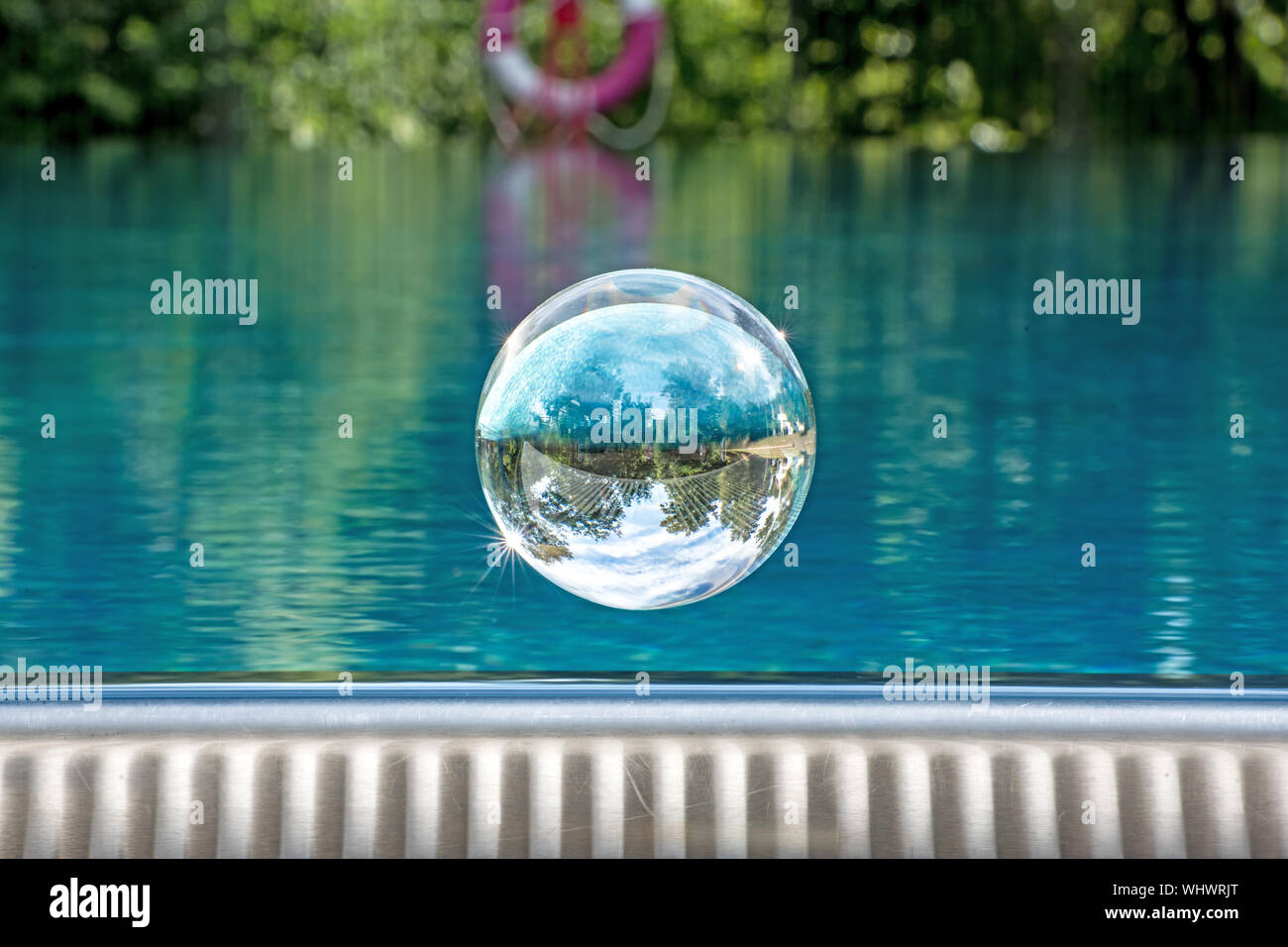 Glass ball hovers over a swimming pool with mirrored cloudy ...