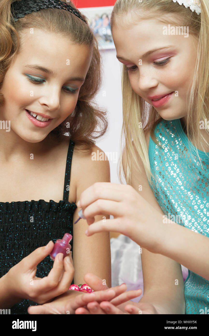 Closeup of a young girl applying nail polish to friend's fingernails Stock Photo