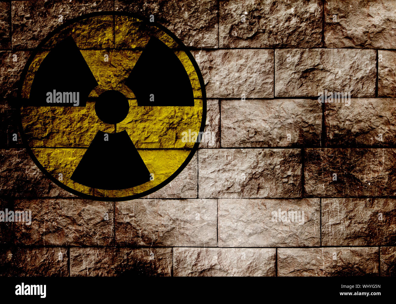 Radiation sign on a brick wall. Stock Photo