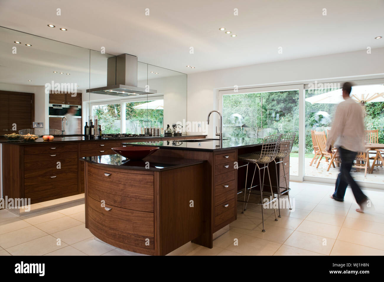Blurred Man Walking In Modern And Spacious Kitchen With Dining Area In The Porch Stock Photo Alamy