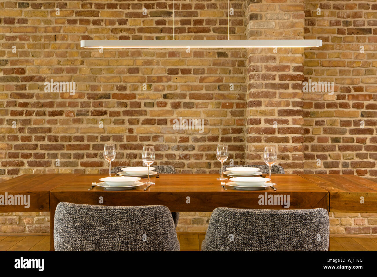 View Of Wineglasses And Plates On Dining Table Against Brick Wall In Modern House Stock Photo Alamy