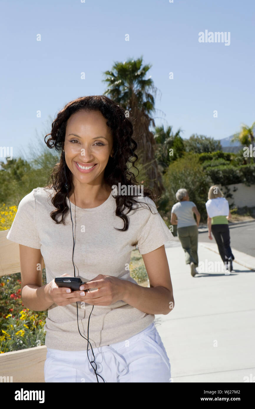 Portrait of a happy woman listening to music with women jogging in the background - Stock Photo