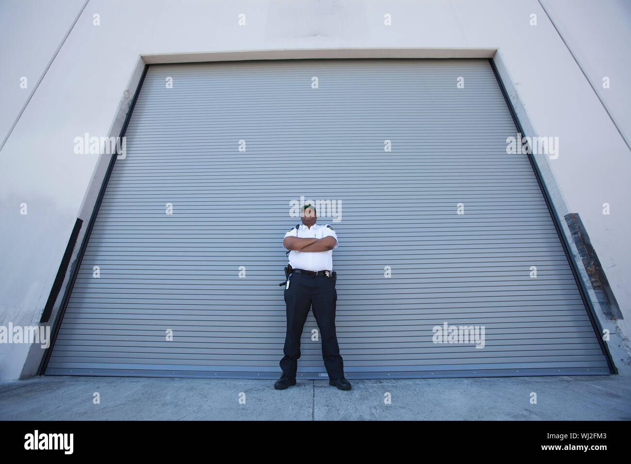 All Guard Shutters low angle view of a young security guard standing with arms