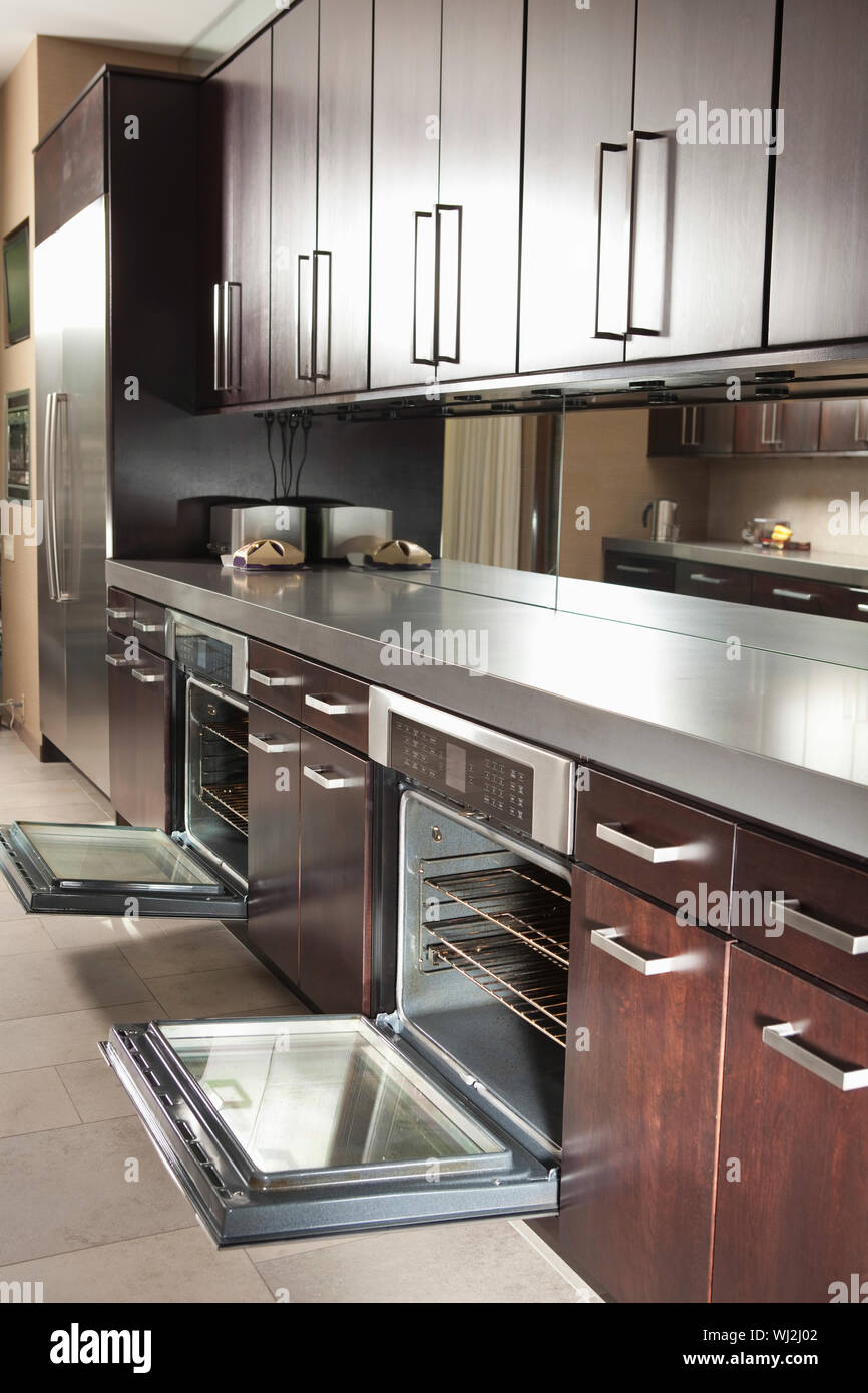 Interior of empty commercial kitchen with open oven and ...