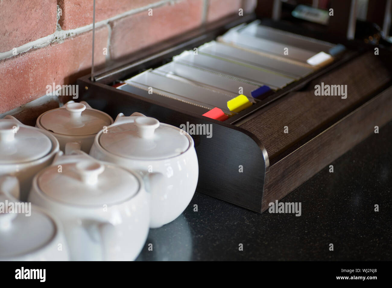 Little China Teapots Lined Up Next To Tea Sachets On Kitchen