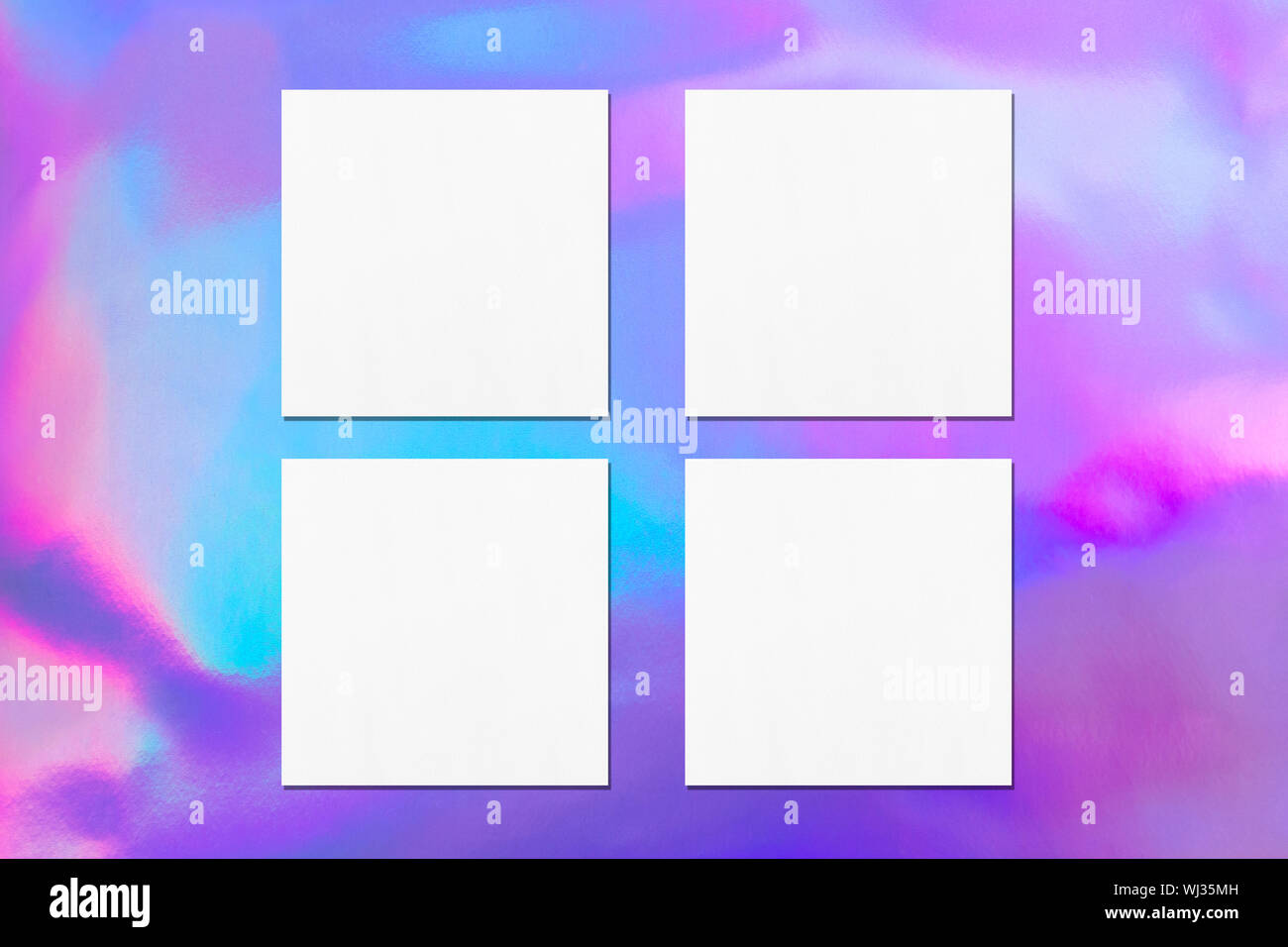 Four empty white square flyer or business card mockups with soft shadows on holographic background. Flat lay, top view Stock Photo