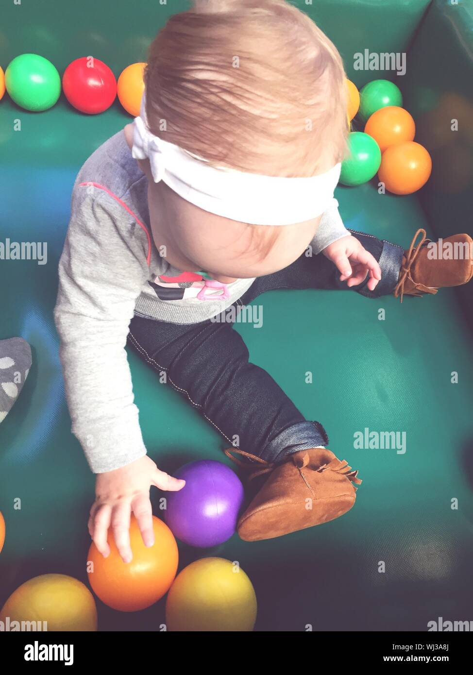 High Angle View Of Baby Boy Playing With Colorful Balls In Ball Pool Stock Photo