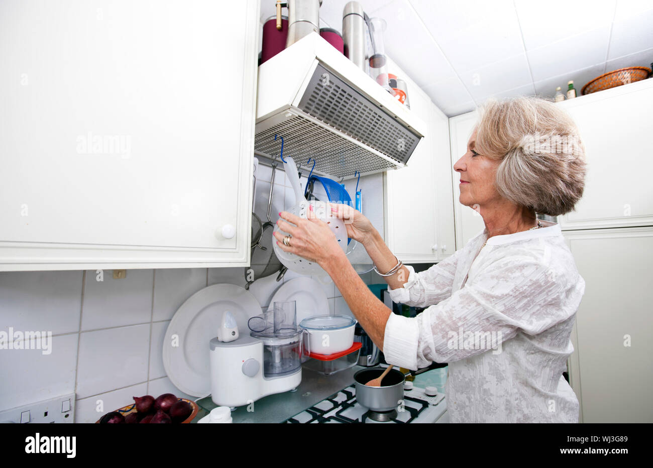 Senior woman hanging colander in domestic kitchen Stock Photo