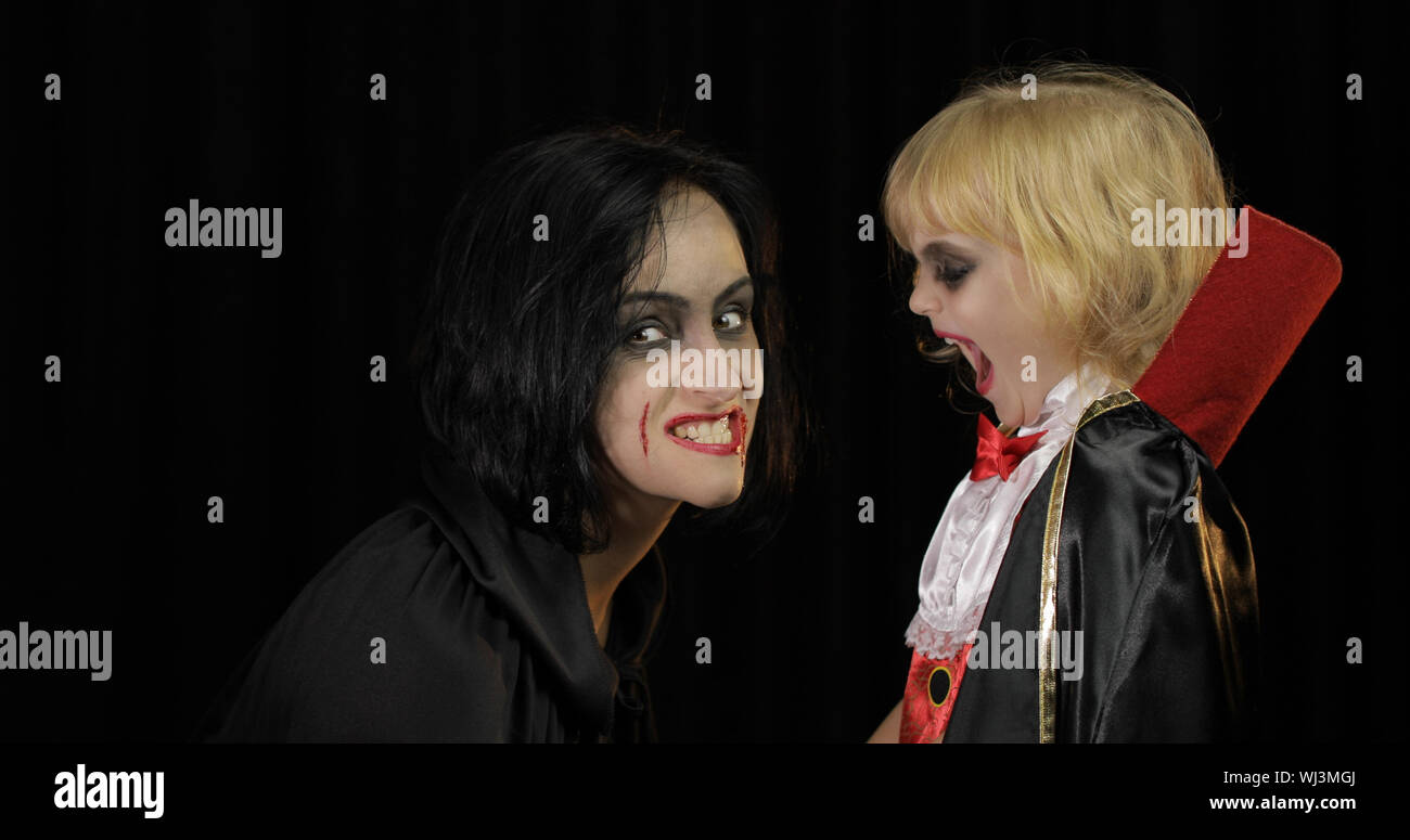 Woman and child dracula making faces. Little girl with her mother. Halloween make-up. Vampire kid with blood on her face. Happy Halloween holiday horror concept. Friday 13th theme Stock Photo