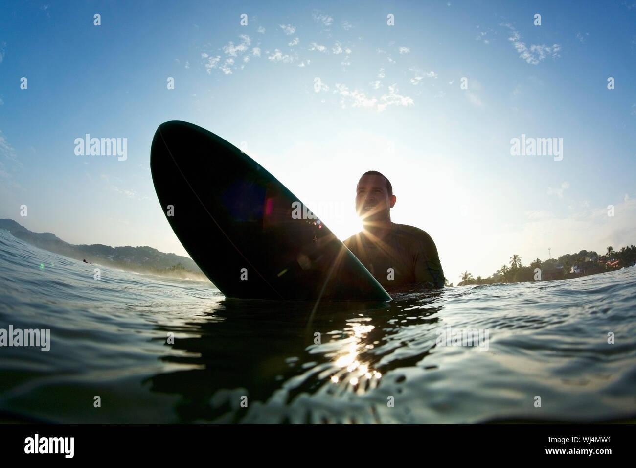 Silhouette male surfer straddling surfboard in sunny ocean Stock Photo