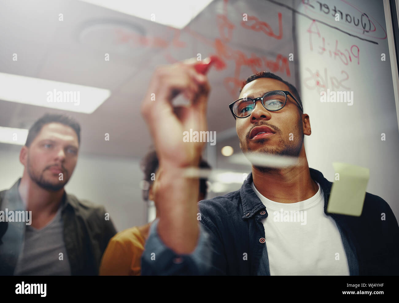 Young creative startup business people in meeting at modern office making plans on transparent glass Stock Photo