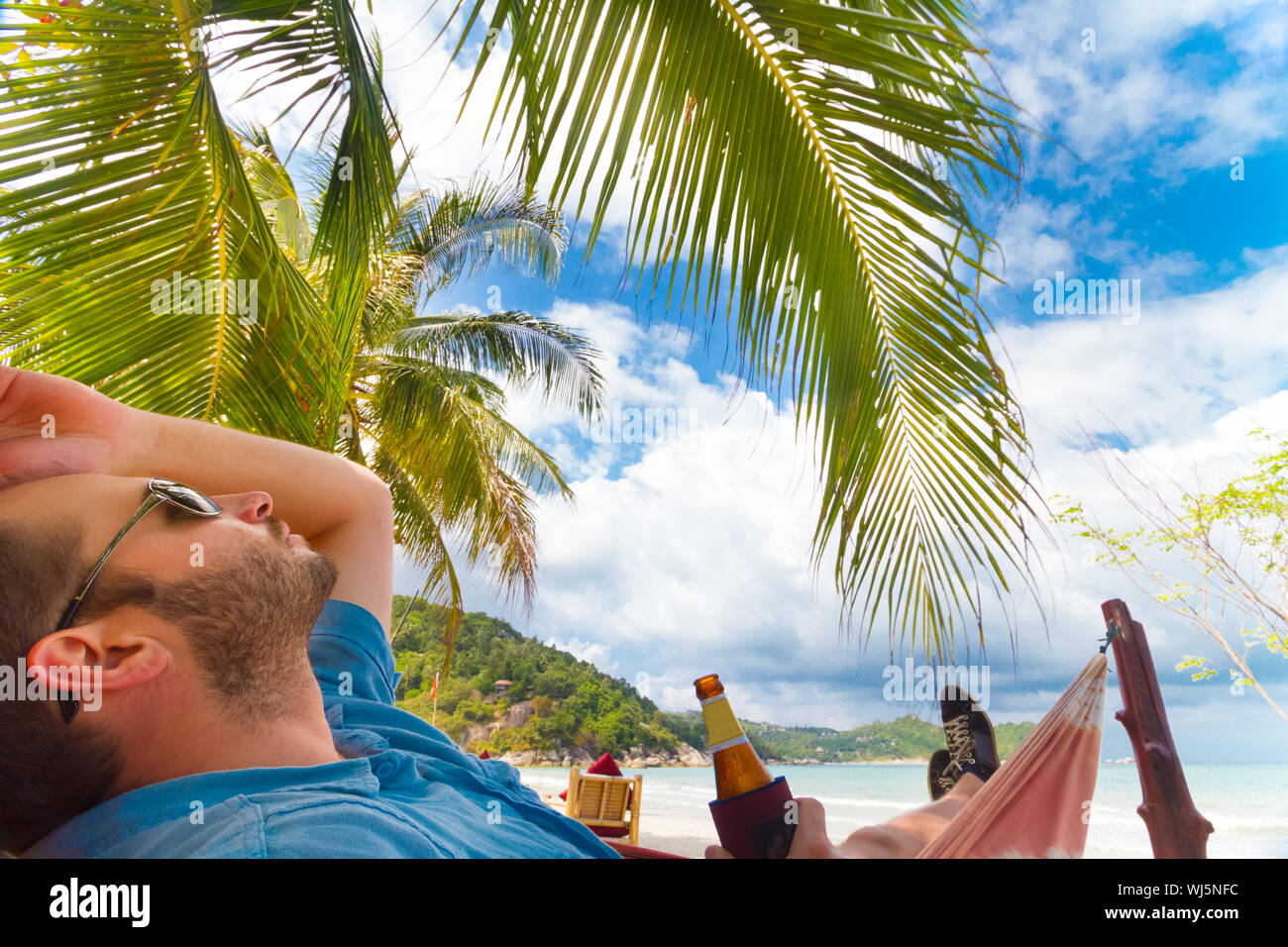 Man Relaxing On A Tropical Beach With A Bottle Of Beer In His Hand Stock Photo Alamy