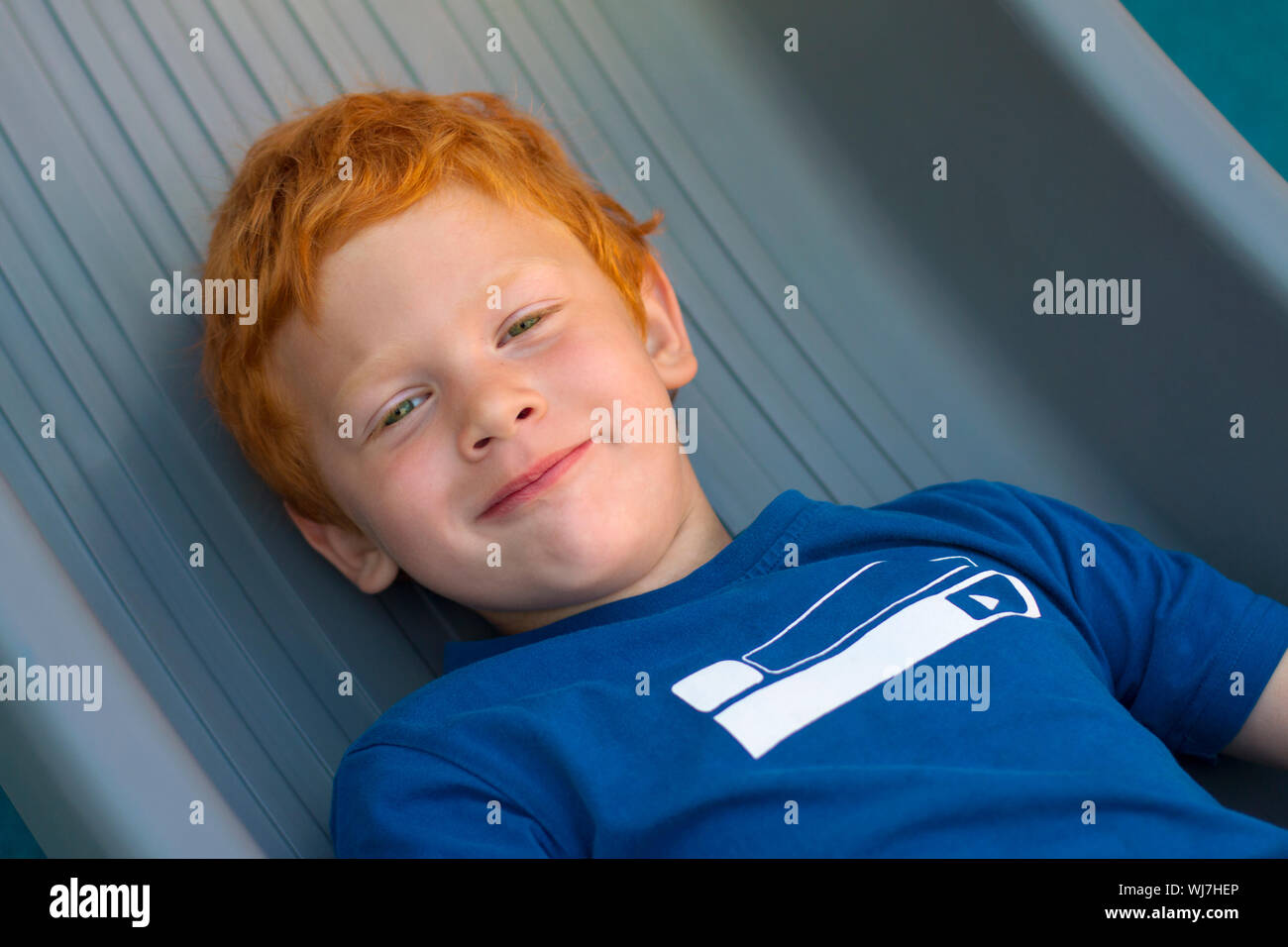 Boy lying on the floor. Portrait European boy with green eyes, looking directly at the camera. Overhead view. Funny little child with curly ginger Stock Photo