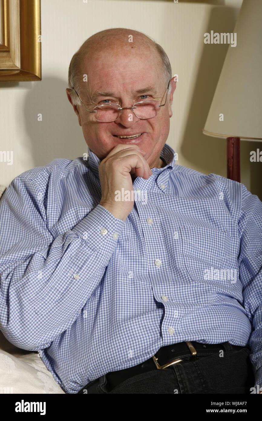 Ein freundlicher, positiver Senior zuhause telefoniert,mit Laptop Stock Photo