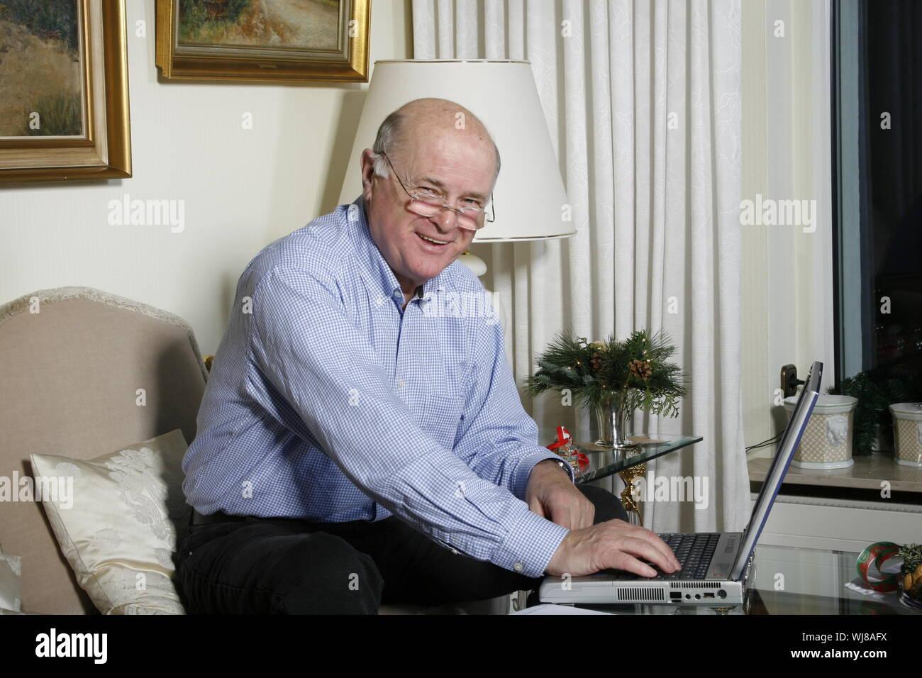 Ein freundlicher, positiver Senior zuhause telefoniert,mit Laptop - Stock Photo