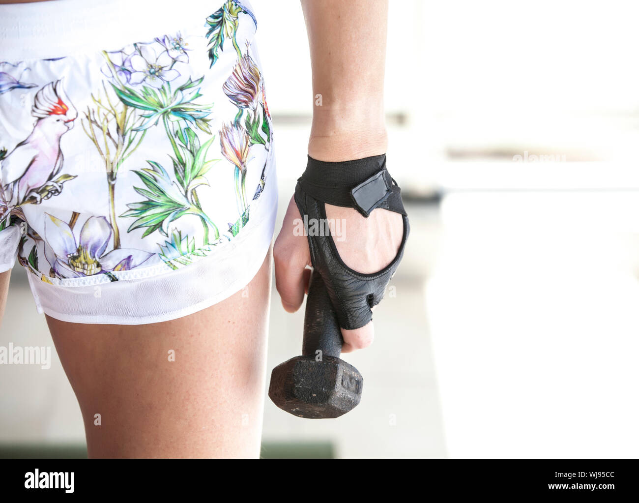 Cropped Image Of Female Athlete Exercising With Dumbbell At Gym Stock Photo