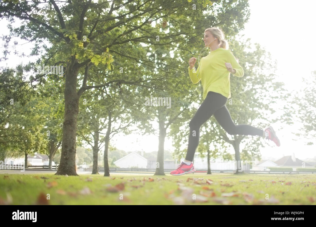 Active pretty blonde jogging in a park on a sunny day Stock Photo