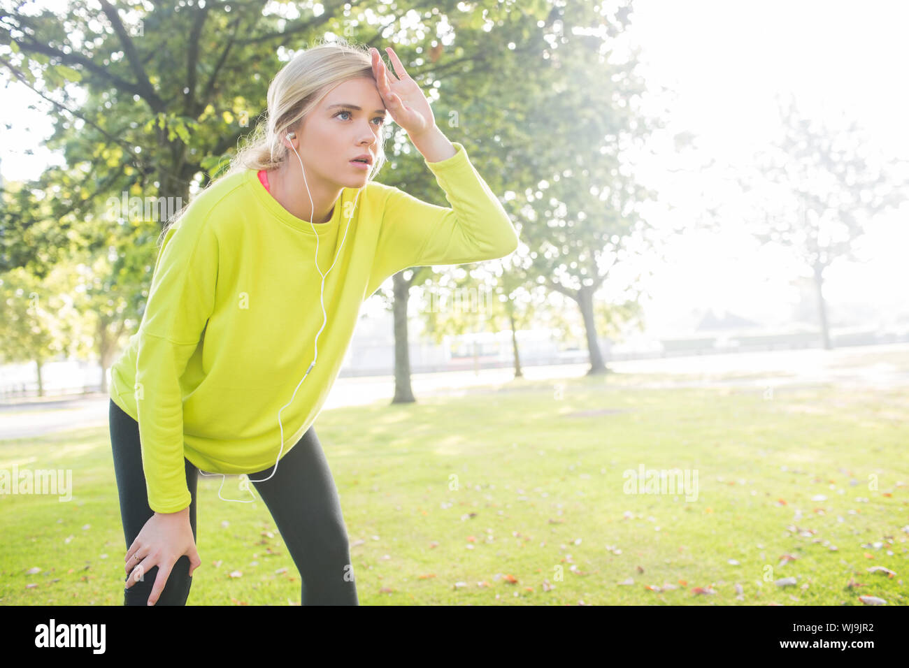 Active exhausted blonde pausing after running in a park on a sunny day Stock Photo