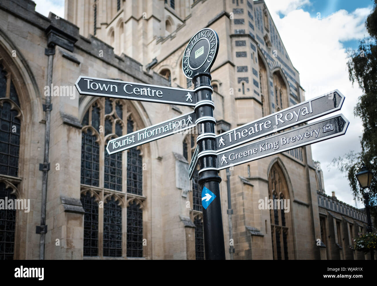 Signpost for Theatre Royal and Greene King Brewery in front of St Edmundsbury Cathedral, Bury St Edmunds, Suffolk, UK Stock Photo
