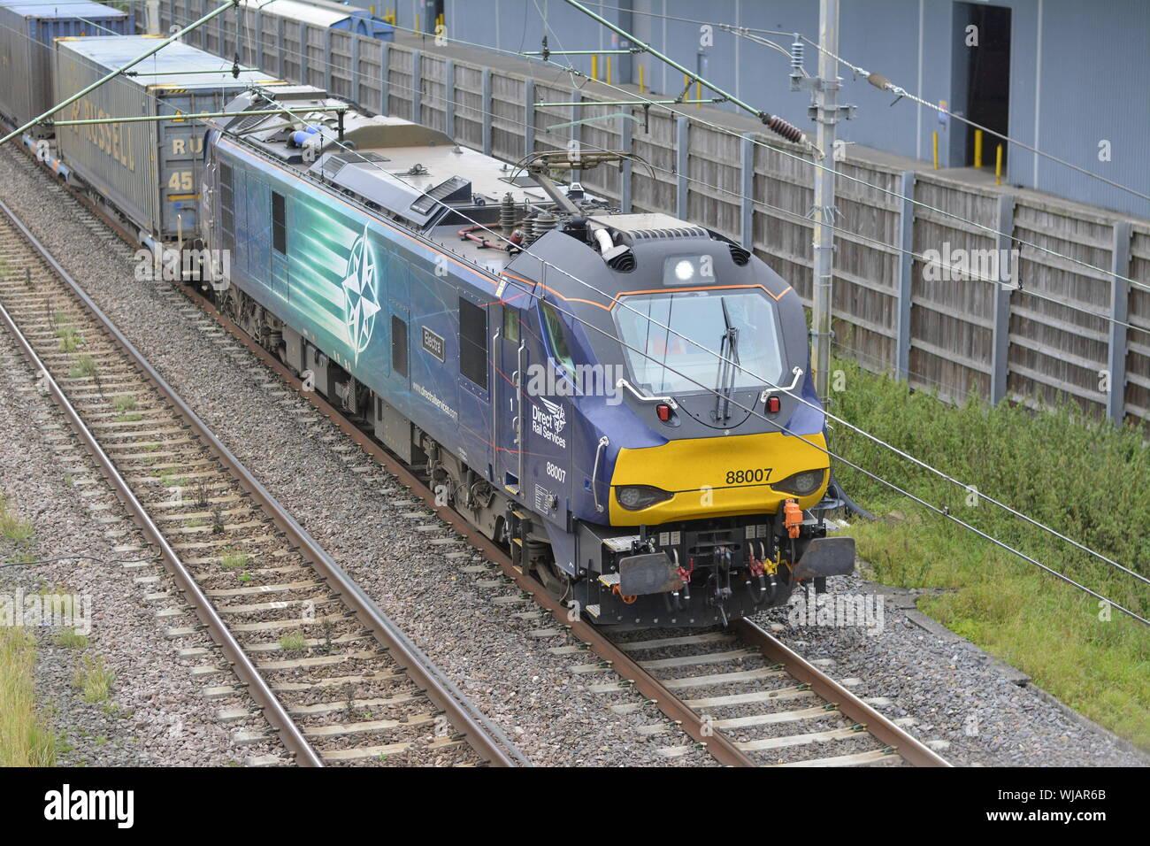 DRS Class 88 bimode locomotive 88007 Electra approaches Daventry International Rail Freight Terminal with an intermodal freight train Stock Photo