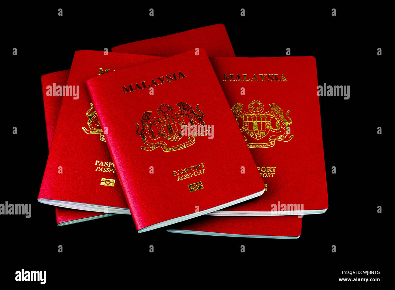 A stack of Malaysian passports isolated on a black background - Stock Photo