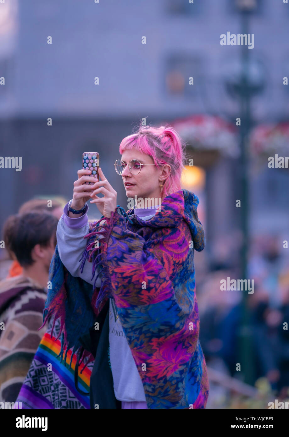 Girl taking a picture with a smart phone, Menningarnott or Cultural day, Reykjavik, Iceland.  Girl looking at her smart phone, Menningarnott or Cultur Stock Photo