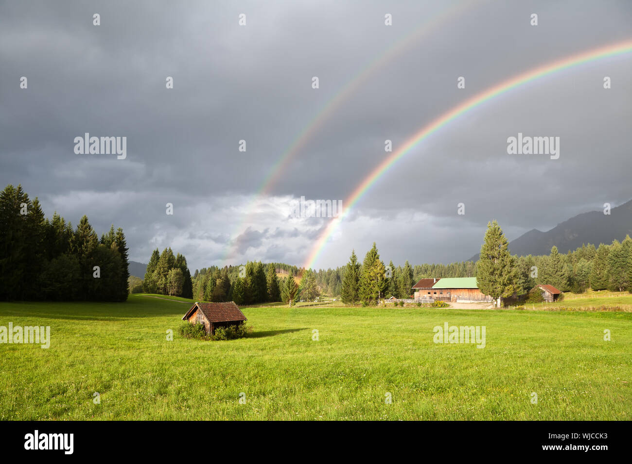 colorful rainbow during rain in Alps, Bavaria, Germany Stock Photo