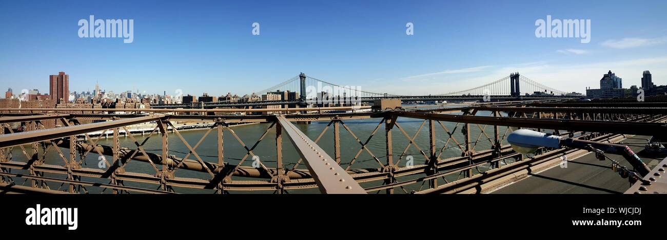 Panoramic View Of Manhattan Bridge Over East River Against Sky Seen From Brooklyn Bridge Stock Photo