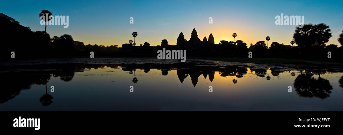 Silhouette of ancient ruins, reflected in water at sunset. Stock Photo