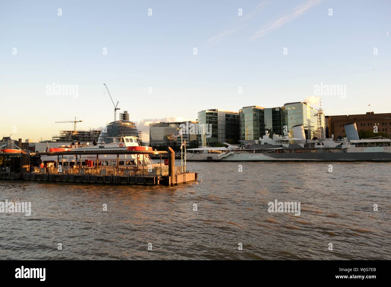 London/UK - August 31, 2014: Panoramic view to the embankment on the  Thames river, the cityscape and HMS Belfast at sunset. Stock Photo