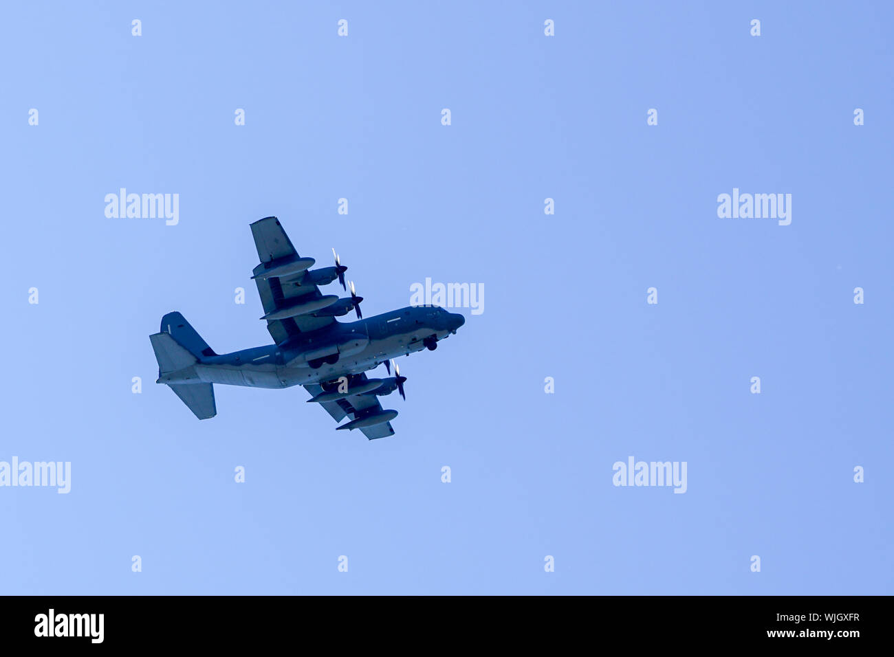 grey military transport plane fly on blue sky background Stock Photo
