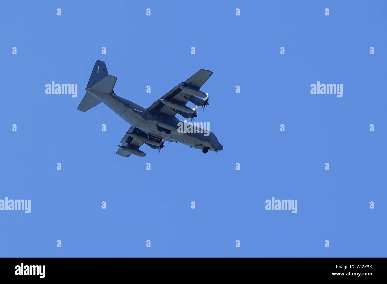grey military transport plane fly on blue sky background - Stock Photo