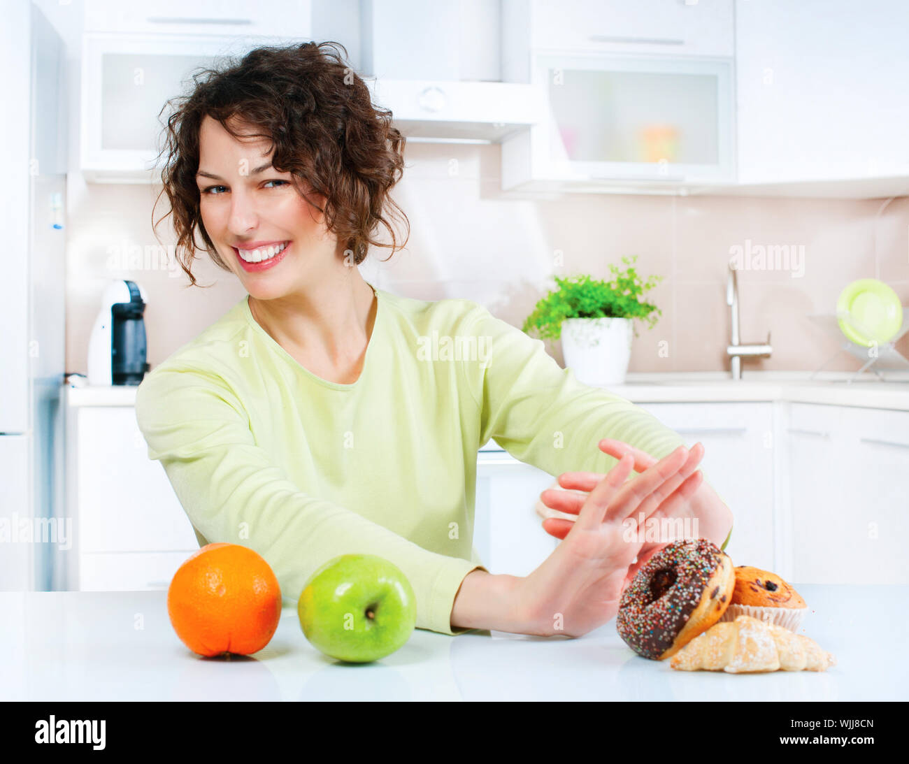 Dieting concept. Young Woman choosing between Fruits and Sweets Stock Photo