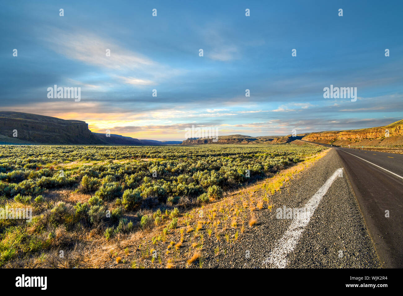 Long road winding though the flat desert brush land into the mountains of the Inland Northwest of rural Washington State in the American Desert Stock Photo