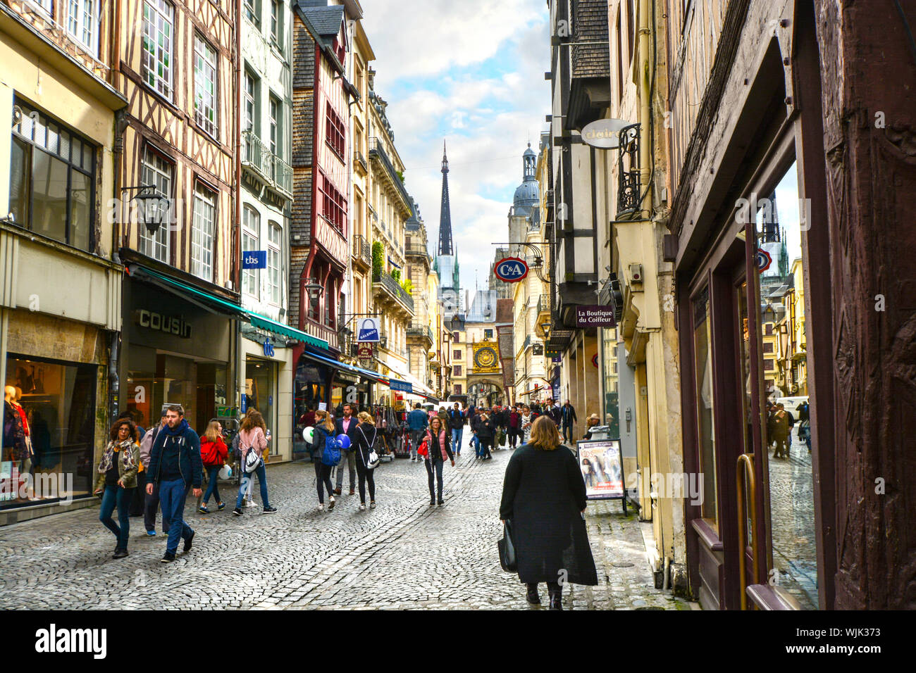 Tourists and locals enjoy a walk on the famous Rue du Horloge, the main tourist shopping street near the medieval Astronomical Clock in Rouen, France Stock Photo