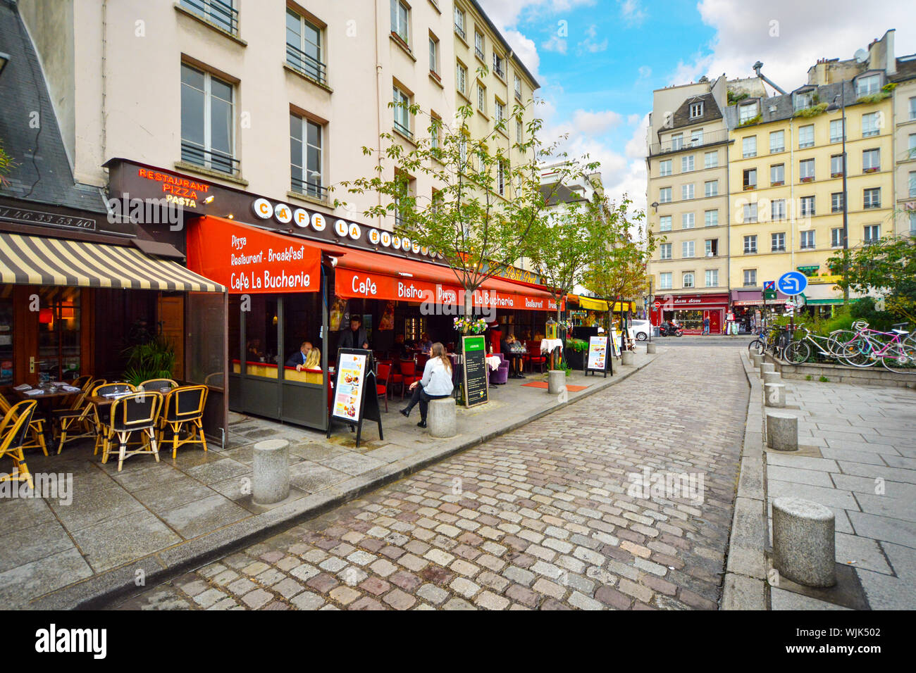 A typical Parisian Latin Quarter bistro with sidewalk cafe seating on an early morning in the 4th arrondissement of Paris France. Stock Photo