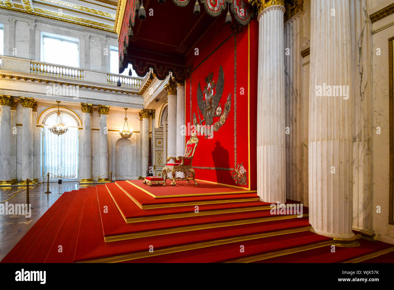 Steps lead up to the red ornate throne surrounded by columns in Catherine Palace in the town of Tsarskoye Selo, or Pushkin, Russia. Stock Photo