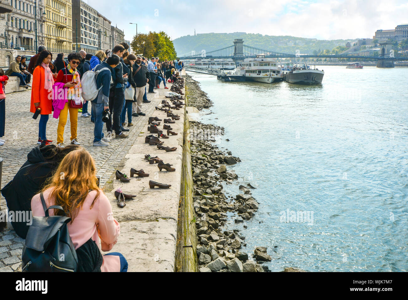 Tourists visit and take photos at The Shoes on the Danube Bank, a memorial in Budapest, Hungary with the Chain Bridge and boats in view Stock Photo